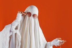 Happy Halloween. Cute funny Ghost on a bright orange background. Sheet Ghost costume, Halloween party carnival. Lovely ghost