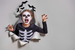 Happy Halloween! Cute little laughing girl in skeleton costume on grey wall background.
