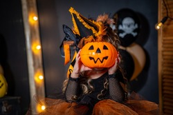 Happy Halloween! Cute little witch with a pumpkin for a head in a dark room. the child is preparing for Halloween. the kid is scared with a lantern in the form of a pumpkin in his hand. Trick or treat
