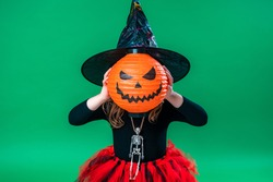 Happy Halloween! Cute little witch with a pumpkin for a head on a green background. child is preparing for Halloween. kid is scared with a lantern in the form of a pumpkin in his hand. Trick or treak