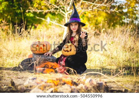 Stock Photo Happy Halloween. Cute little witch with a pumpkin in the hands of the fire. Beautiful young child girl in witch costume outdoors.
