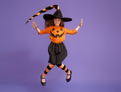 Happy Halloween! Cute little witch with a pumpkin on violet background.