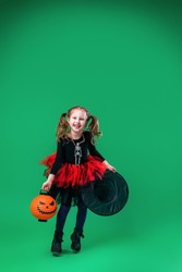 Happy Halloween! cute little witch with pumpkin and hat in her hands jumps on green background. child is preparing for Halloween. kid with pumpkin-shaped lantern in her hand.