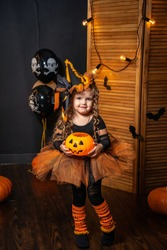 Happy Halloween! Cute little witch with pumpkin with pumpkin stands on background holiday decorations. child is preparing for Halloween. kid is scared with lantern in form pumpkin in his hand