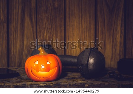 Happy Halloween festival background concept. Close up of Halloween head Pumpkins doll and the black iron dumbbell and equipments. Fitness, healthy active lifestyle on Halloweeen day concept.