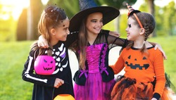 Happy Halloween! funny kids girls laughing in fancy dress outdoors
