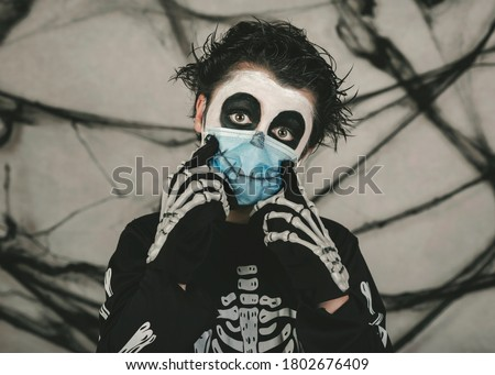 Happy Halloween,kid wearing medical mask in a skeleton costume making smile over gray background Photo stock ©