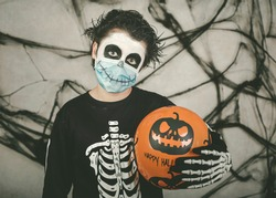Happy Halloween. kid wearing medical mask in a skeleton costume with halloween 