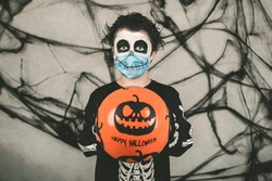 Happy Halloween,kid wearing medical mask in a skeleton costume with halloween balloon over gray background