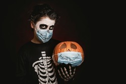 Happy Halloween.kid wearing medical mask in a skeleton costume with halloween pumpkin over dark background