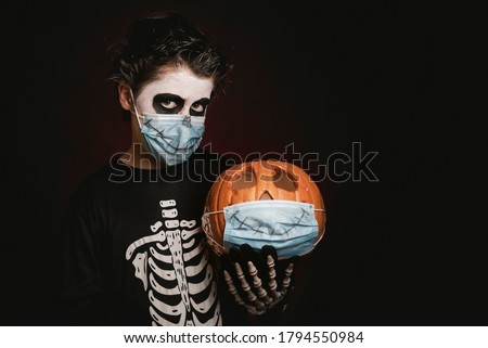 Happy Halloween.kid wearing medical mask in a skeleton costume with halloween pumpkin over dark background