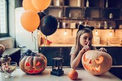 Happy Halloween! Little cute girl is preparing for Halloween. Having fun with pumpkins on kitchen with cat Halloween makeup.