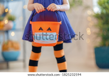 Happy Halloween! Little kid with a basket for sweets  wearing face mask protecting from COVID-19.