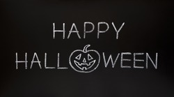 Happy Halloween made with white chalk on a blackboard.