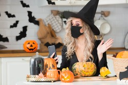Happy Halloween. Online greetings. A woman wearing a black medical mask and a witch costume uses a mobile phone to make video calls to friends and parents.