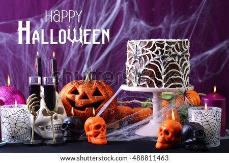 Happy Halloween Party Table with chocolate spider web cake and burning candles against purple spider web background.