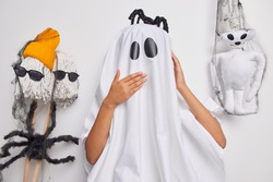Happy Halloween. Scarying creepy ghost wears costume for halloween carnival poses around spooky creatures going to celebrates 31st of October prepares for mysterious night. Trick or treat concept