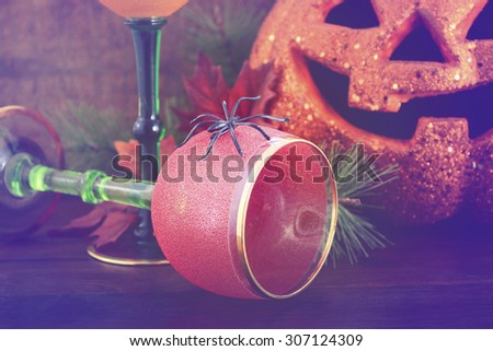 Happy Halloween table with Jack O Lantern pumpkin with party wine goblets on rustic dark wood vintage background with added vintage style filters.