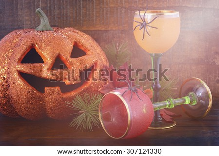 Happy Halloween table with Jack O Lantern pumpkin with party wine goblets on rustic dark wood vintage background with added vintage style filters and lens flare.