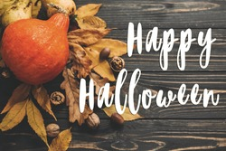 Happy Halloween Text on Beautiful Pumpkin with bright autumn leaves, acorns, nuts on wooden rustic table, flat lay. Atmospheric image. Seasons greeting card.