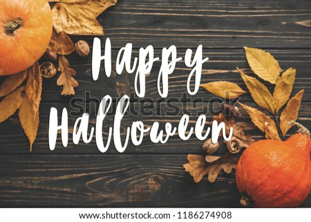 Happy Halloween Text on Beautiful Pumpkin with bright autumn leaves, acorns, nuts on wooden rustic table, flat lay. Atmospheric image. Seasons greeting card. #1186274908
