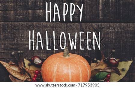 happy halloween text sign, greeting card. fall image flat lay. beautiful pumpkin and leaves and berries on rustic wooden background, top view. cozy autumn mood. fall holiday - Shutterstock ID 717953905