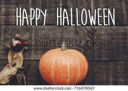 happy halloween text sign, greeting card. simple fall image flat lay. beautiful pumpkin on rustic wooden background, top view. cozy autumn mood. fall holiday #716878069