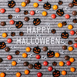 Happy Halloween text with decoration paper pumpkins and candy on a gray background.