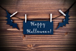 Happy Halloween written on a Tag on a Wooden Background