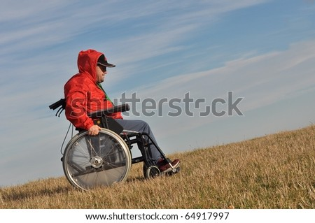 Happy handicapped man on a wheelchair over a green meadow