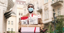 Happy handsome African American man in snowy city with many christmas gift boxes after xmas shopping. Portrait of joyful grateful male in mask holds holiday presents on street. New year's eve concept
