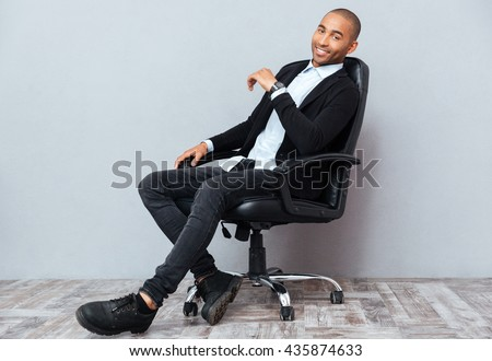 Happy handsome african american young man sitting in leather office chair