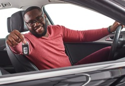 Happy handsome african man showing car keys in his newly bought auto smiling cheerfully sitting in the  luxury vehicle copyspace owner ownership sales driving consumerism private taxi concept