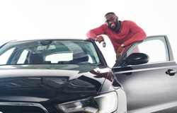 Happy handsome African man showing car keys in near his newly bought vehicle car smiling cheerfully copy space owner ownership sales driving consumerism private taxi concept studio shot