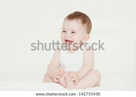 Happy handsome baby boy laughing and showing his first teeth