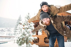 Happy handsome bearded man piggibacking his girlfriend and laughing in winter