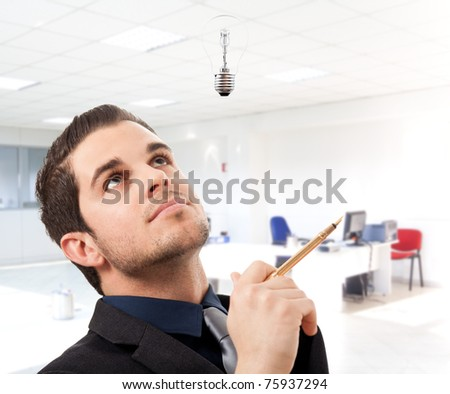 Happy handsome businessman having a good idea in an office environment.