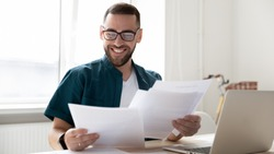 Happy handsome businessman holding and reading documents with good news near laptop. Young smiling bearded man, student rejoice and celebrate successful distance deal for work.