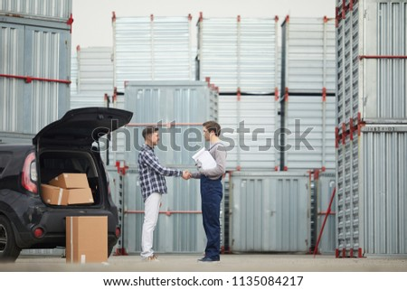 Happy handsome customer in casual clothing shaking hand of storage manager with clipboard after discussing contract about rent of container