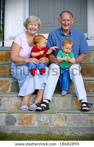 Happy handsome grandparents with twin grandsons outdoor portrait