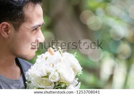 Happy handsome groom man with casual suit hold beautiful floral bouquet wait for his future bride and ask for commitment to get marriage / wedding and marriage commitment concept #1253708041
