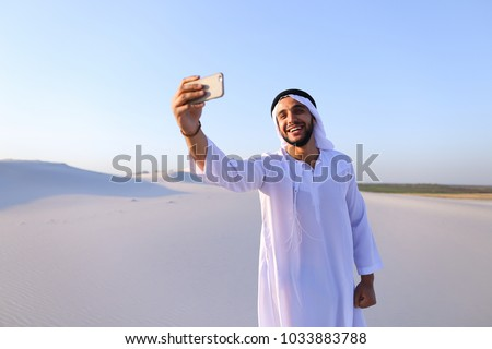 Happy, handsome guy, emirate and tourist, conducts dialogue through Internet with help of device, waves hand and smiles at camera of smartphone, shows beautiful views and sights of large sandy desert #1033883788