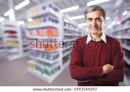 Happy handsome man at grocery store products