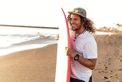 Happy handsome man having fun, standing with surfboard on the beach. Smiling surfer. Hobby. Summer time. Island vibes. Real people lifestyle and extreme sport concept