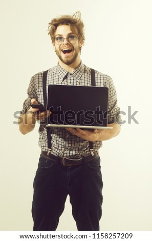 Happy handsome man or male student, businessman, with beard and stylish, blond hair, in nerd glasses talking on smartphone with laptop computer. Communication and using technology #1158257209