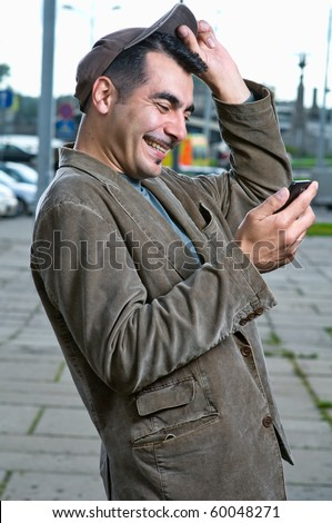 Happy handsome man with mobile phone outdoors