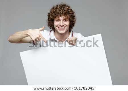Happy handsome smiling man with banner, over gray background