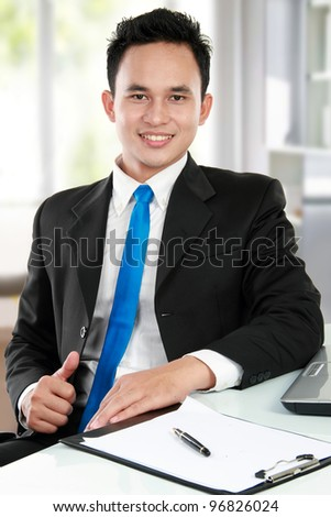 Happy handsome young asian business man at the office