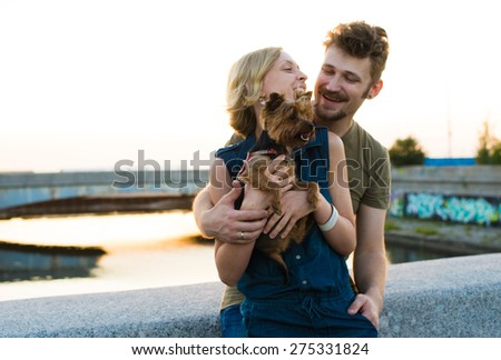 happy handsome young couple with small dog embracing and laughing