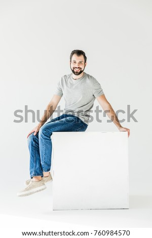 happy handsome young man smiling at camera while sitting isolated on white